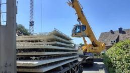 Kraanwagen van kvn op een bouwplaats tilt elementwanden en elementplafonds